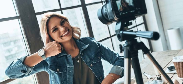 Young and smart. Beautiful young woman in casual wear smiling while recording video
